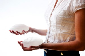 woman holding two breast implants